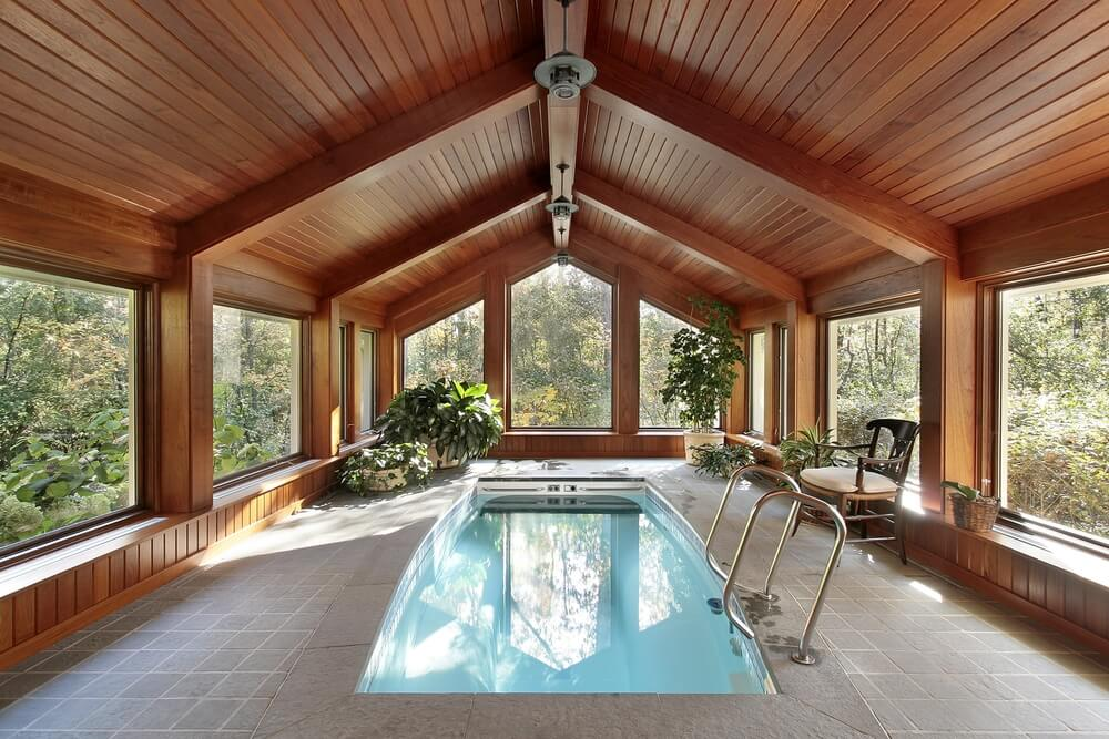 All wood and glass indoor pool wing. Ceiling and part of the walls in wood. Pool is fairly small in size. Windows surround the space bringing in plenty of natural light.