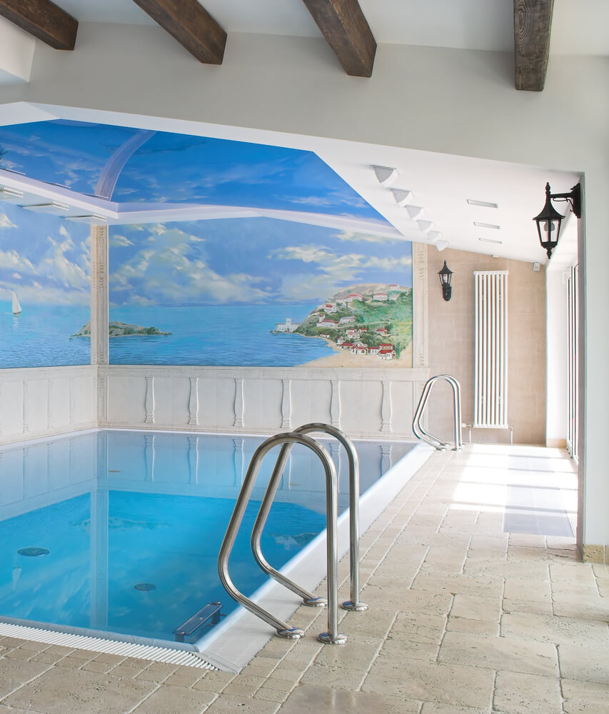 Small in ground interior pool with ocean mural on two walls.