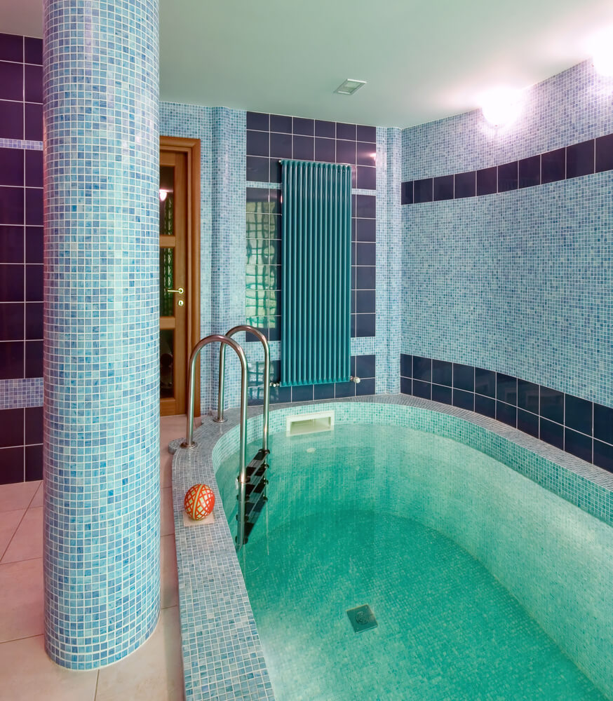 Small oval interior pool room with extensive blue tile work on the walls and pool.