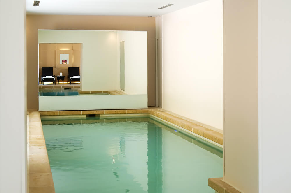 Small indoor pool with large mirror on one end giving the illusion of a larger space.