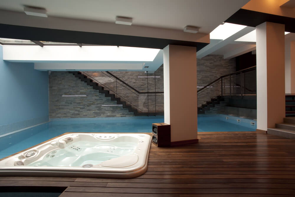 Modern underground indoor pool and hot tub with wood deck and brick wall.