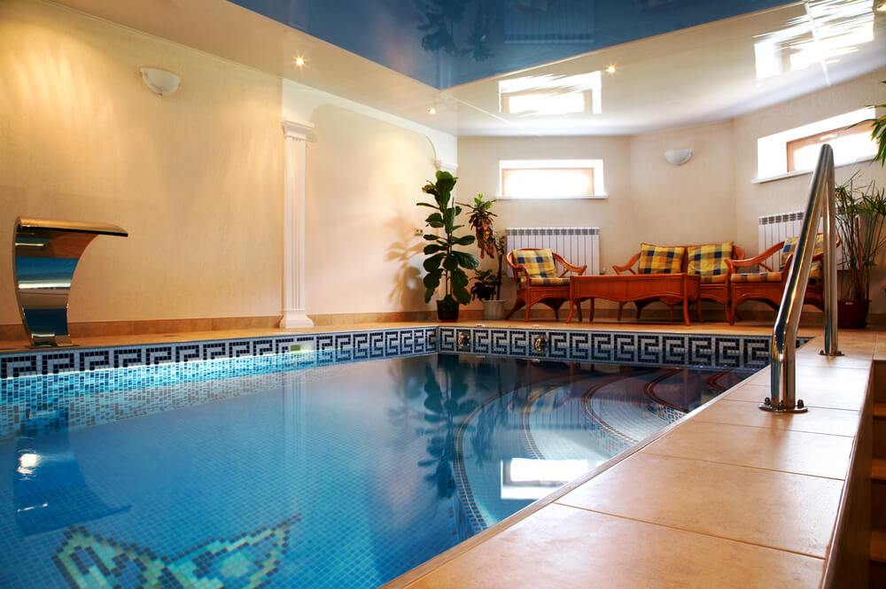 Indoor pool room with blue ceiling peach walls and sitting area.