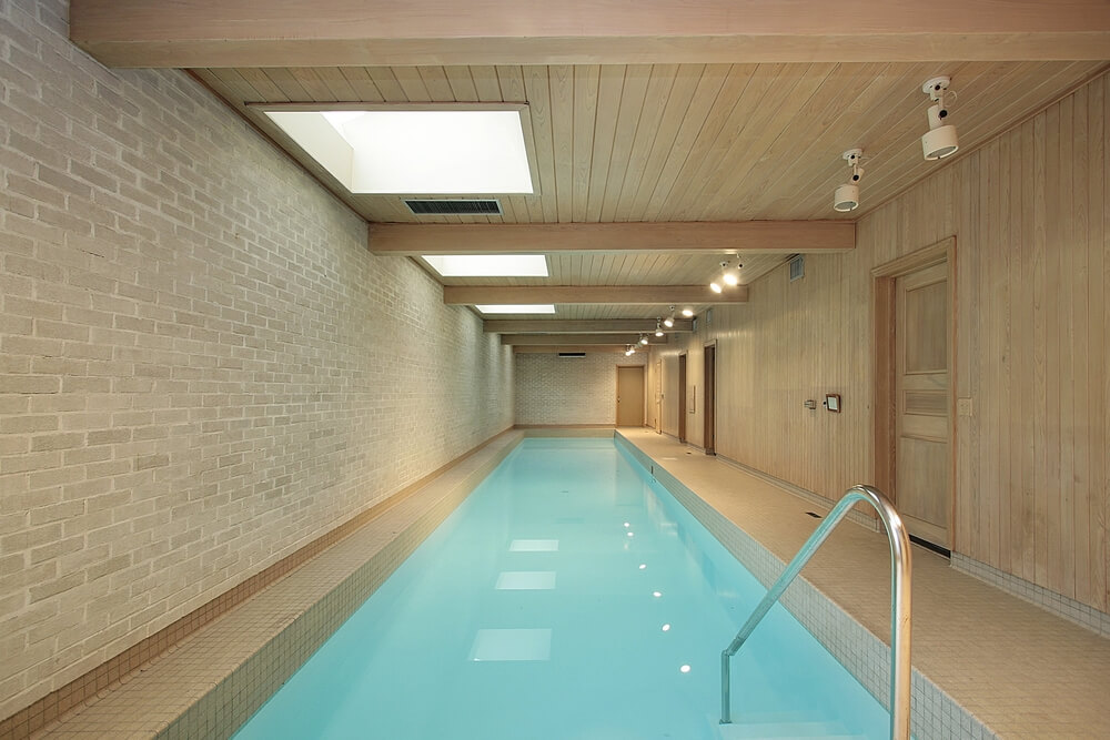 Modern indoor lap pool with brick wall and wood wall. Wood ceiling includes skylights for natural light.
