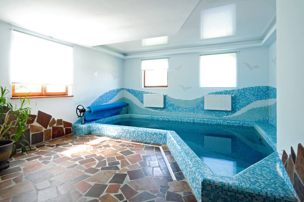 Small indoor pool with blue tile patterns and stone work for a small inside pool deck.