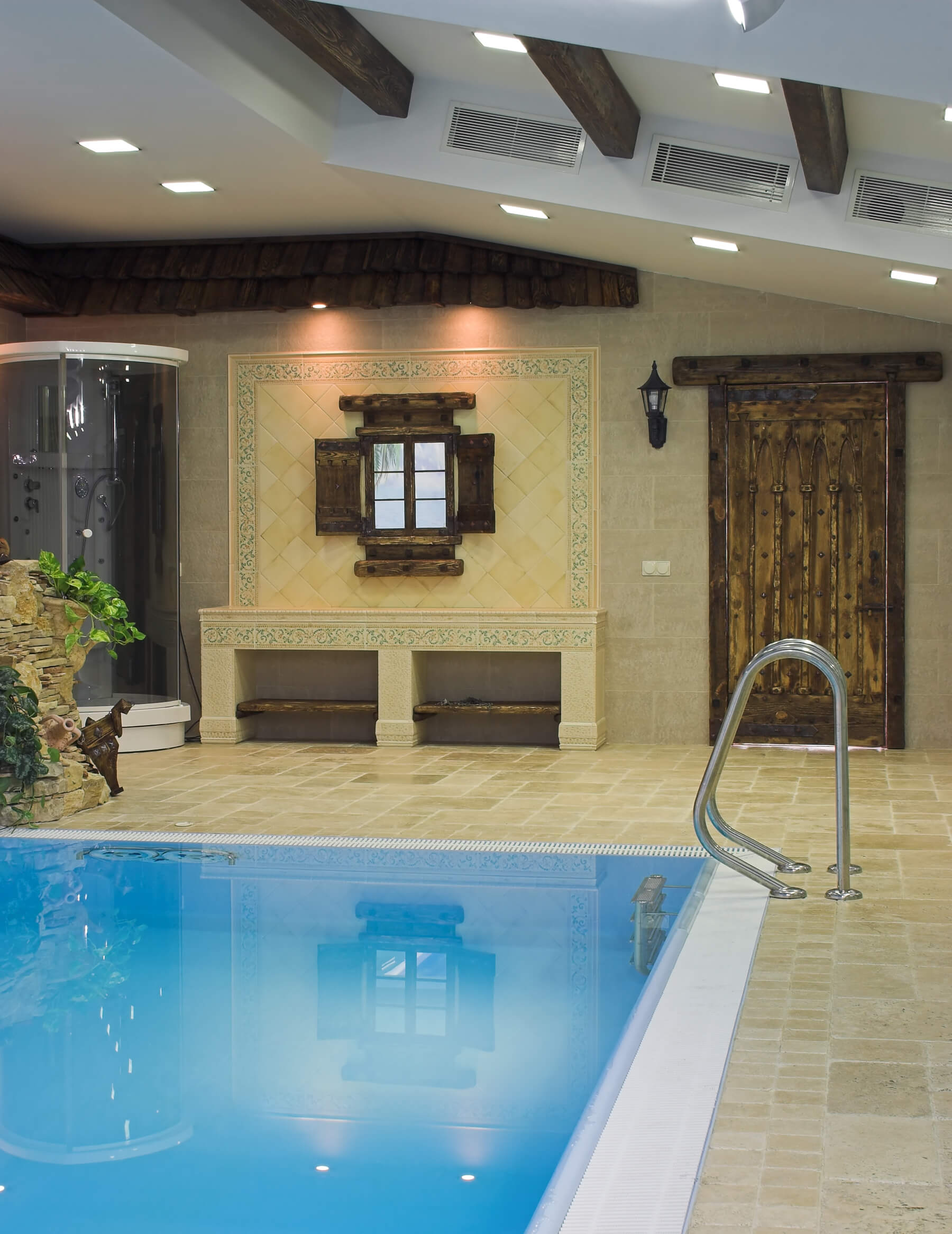 Partial view of pool room with round glass shower, wood door and tile work on the walls.