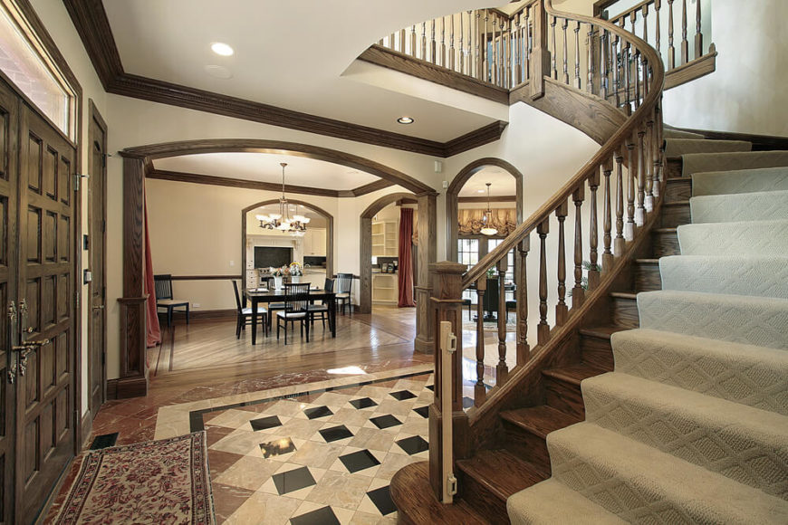 Foyer in older mansion with exposed wood beams, arched wooden staircase with carpet runner.