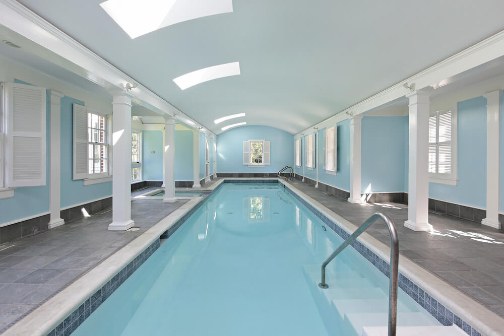 Large indoor pool and hot tub in light blue walls and white support beams and white ceiling. Room design matches the pool colors (blue and white).