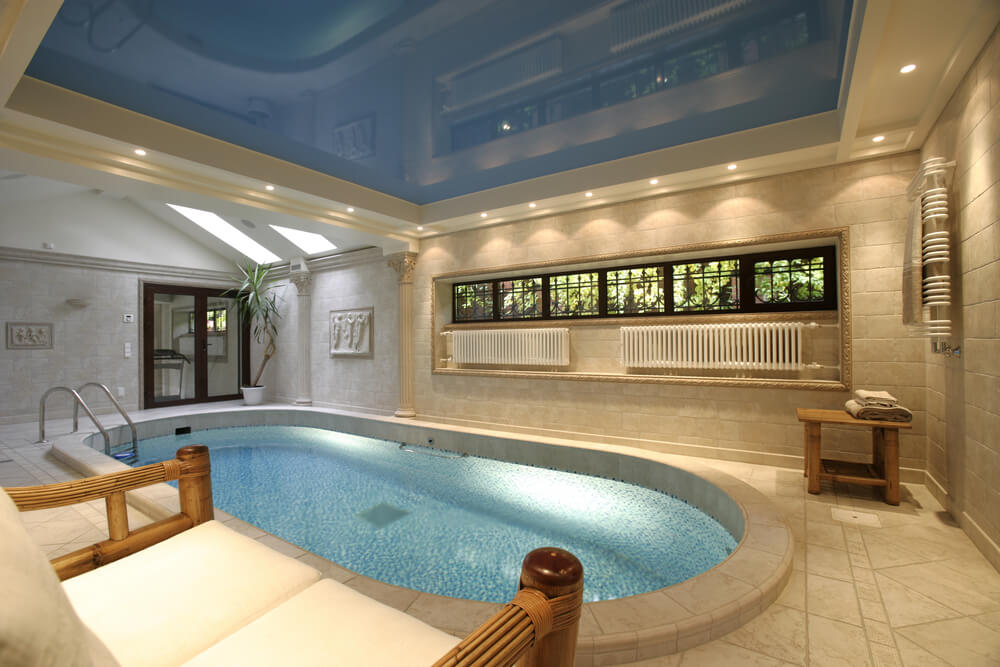 Oval indoor pool with recessed blue ceiling and tile patio surrounding the pool.