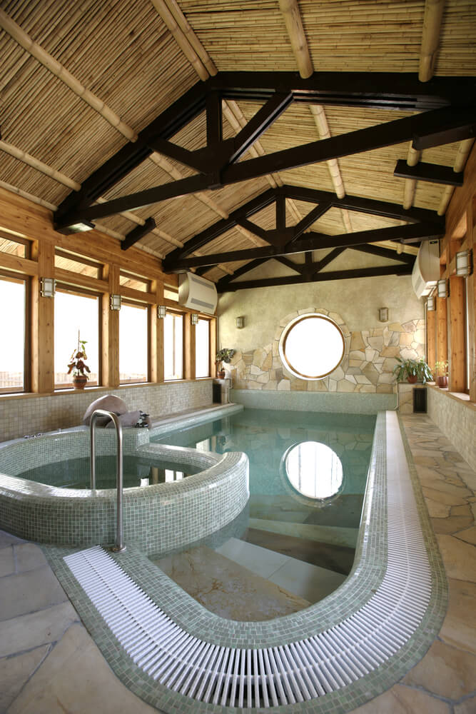Stone, tile and wood indoor pool and hot tub. Exposed wood beams on the ceiling give it a larger spacial appearance. Windows surround the room flooding it with natural light.