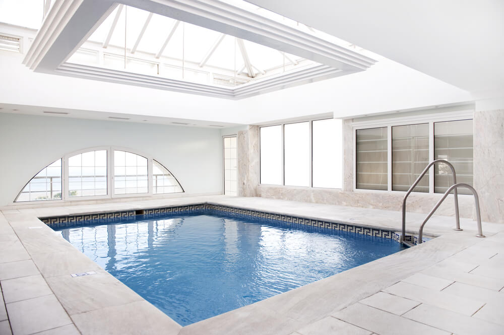 White and light grey interior pool with glass cathedral roof.