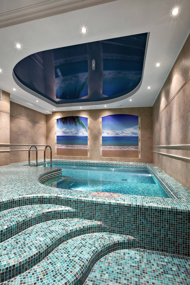 Small interior pool with recessed blue ceiling wall murals of the ocean and intricate tile pattern deck.