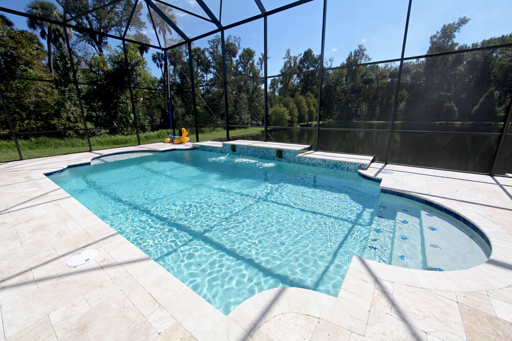 Screened-in swimming pool in a backyard surrounded by a lagoon and trees.