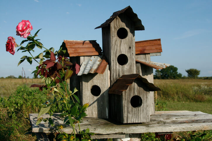 Large wood bird house with metal roof. Room for 4 birds. The structure sits on a wood plank in the middle of a field.
