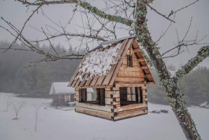 Large log home style bird house with steep roof hanging from a tree.