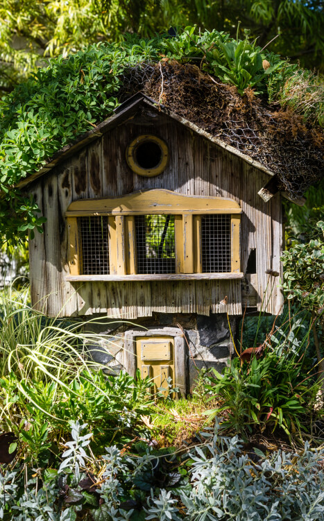 Rustic large wood bird house situated in garden.