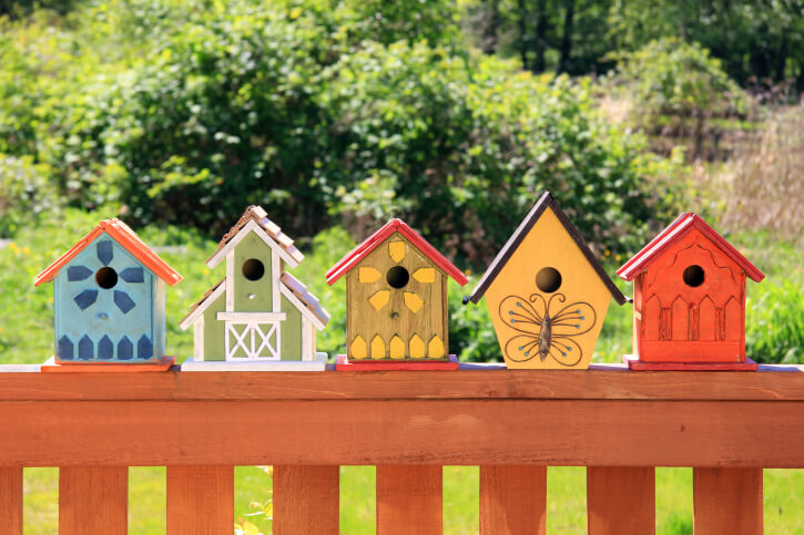 5 colorfully painted bird houses placed on top of a deck railing.