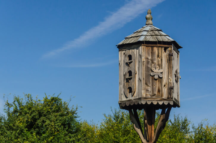 Ornate octagon wood bird house with shingle roof placed on a wooden post.