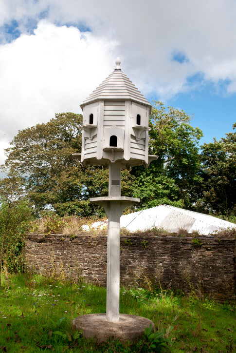 White octagon bird house in a gazebo design placed on a post.