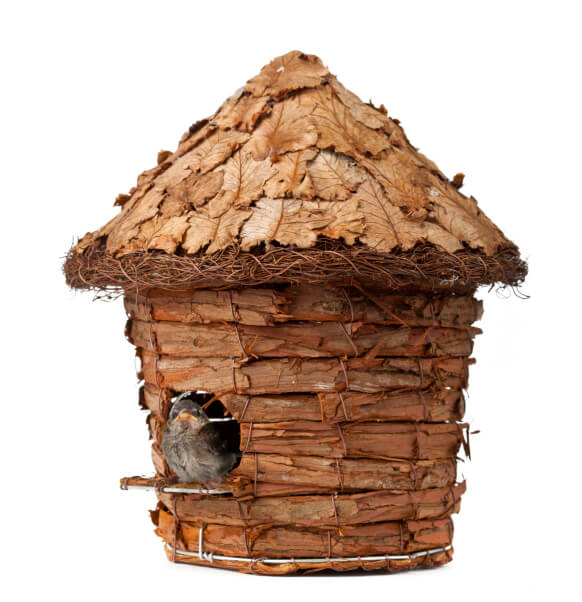 Bird house created with tree bark and wire frame.