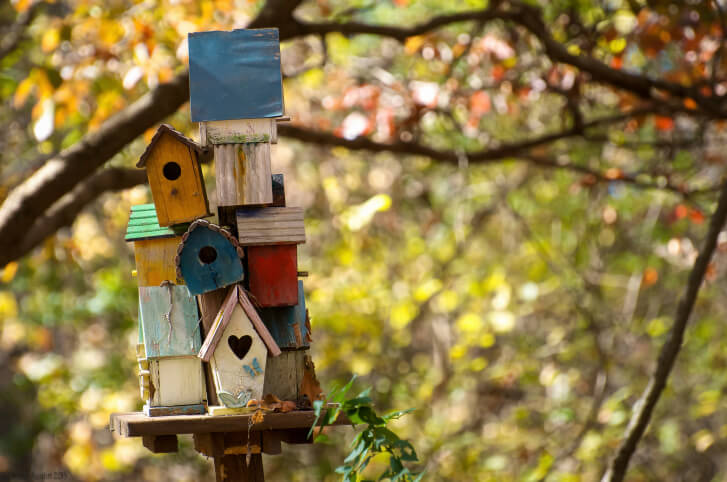 Painted cluster of bird houses structured into a bird house tower. Each are colorfully painted and sits on a wooden post.