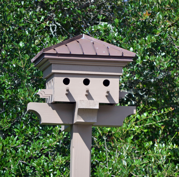 Great example of an intricate bird house that blends well with the post on which it sits.