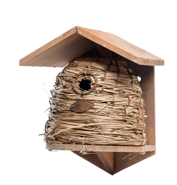 Straw bird house with wooden covering designed in the shape of a bee hive.