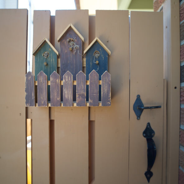 Picture of 3 small bird houses with painted picket fence placed on the gate of a fence.