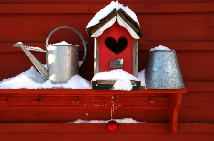 Red bird house on red shelf against a red house with a heart-shaped access hole.
