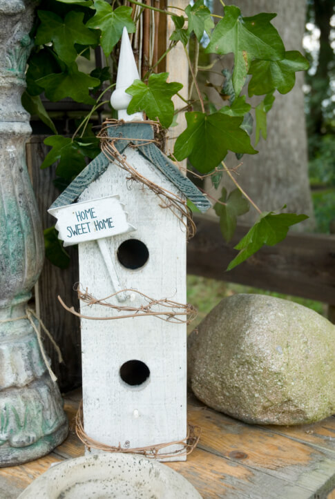 Small white painted bird house with steeple placed next to a large bird bath.