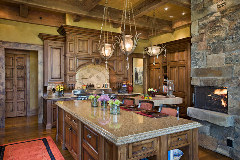 "Kitchen view of island with bar style seating, fireplace, and extensive wood cabinetry. Builder: Schlauch Bottcher Construction Interior Design: <a href=""https://www.locatiarchitects.com/"">Locati Interiors</a> Photography: <a href=""https://www.rogerwadestudio.com/"">© Roger Wade Studio</a>"