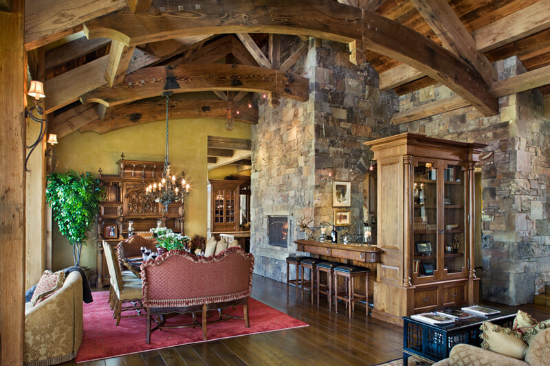 "Dining room with another fireplace, full bar area, and exposed beam arches. Builder: Schlauch Bottcher Construction Interior Design: <a href=""https://www.locatiarchitects.com/"">Locati Interiors</a> Photography: <a href=""https://www.rogerwadestudio.com/"">© Roger Wade Studio</a>"