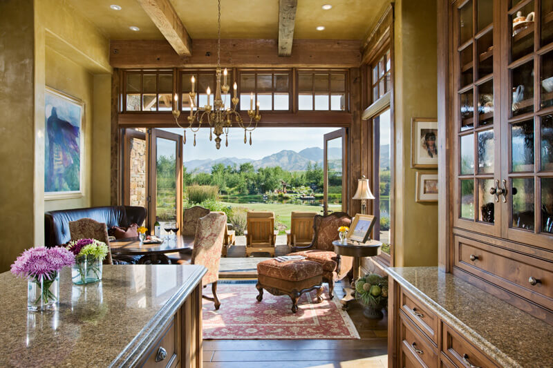 "Kitchen with accordion glass doors open wide to patio. Builder: Schlauch Bottcher Construction Interior Design: <a href=""https://www.locatiarchitects.com/"">Locati Interiors</a> Photography: <a href=""https://www.rogerwadestudio.com/"">© Roger Wade Studio</a>"