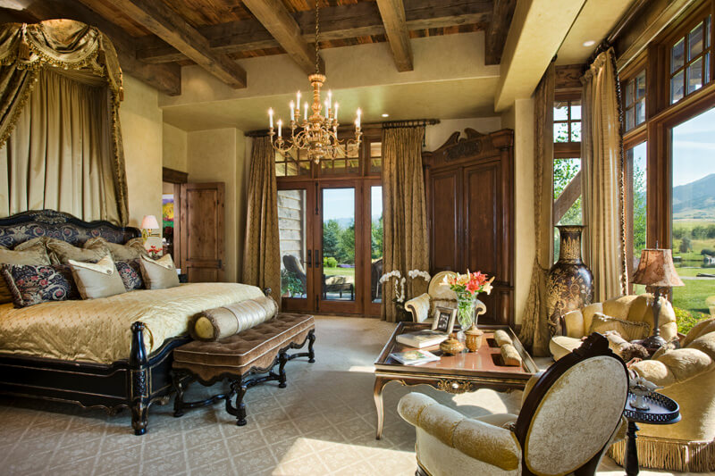 "Primary bedroom with glass French doors to patio, large window view of the estate, and ornate headboard display. Builder: Schlauch Bottcher Construction Interior Design: <a href=""https://www.locatiarchitects.com/"">Locati Interiors</a> Photography: <a href=""https://www.rogerwadestudio.com/"">© Roger Wade Studio</a>"