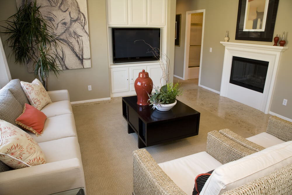Modern living room design with two wicker armchairs, one white sofa, flat screen television placed in custom built-in white cabinets and a small gas fireplace with small white mantle.