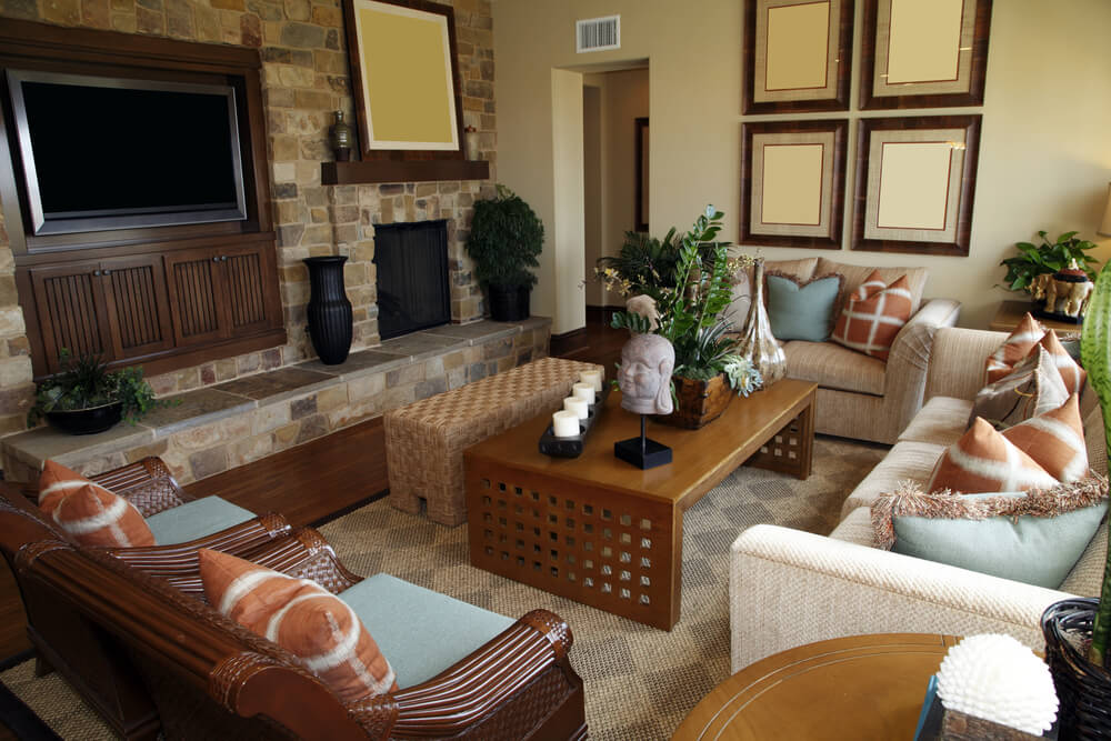 Living room that doubles as family room with one sofa, one loveseat and two ornate wooden chairs all facing flat screen television mounted in wood shelving surrounded by a brick wall.