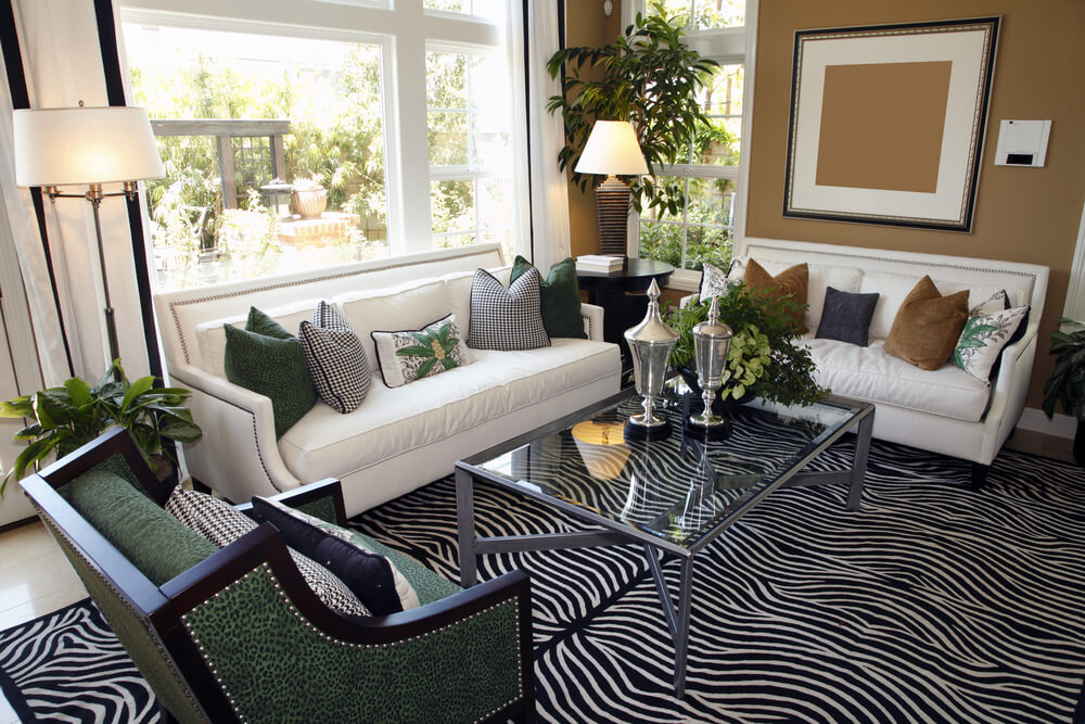 Living room design with two white sofas taupe walls and zebra area rug. Glass coffee table with steel frame squarely situated in between the sofas. Furniture faces gas fireplace and television.