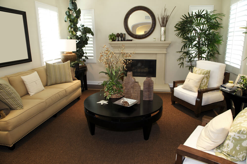 Cozy living room with wood framed armchairs facing a round dark wood coffee table and light brown sofa.