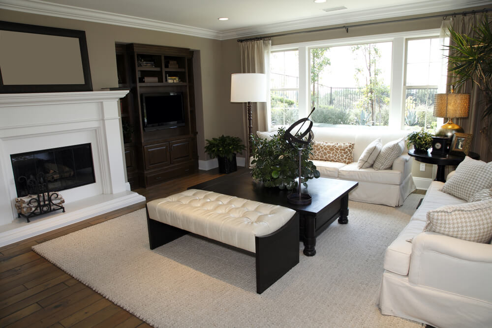 White and dark brown living room design. In addition to two all-white sofas, there is a low dark wood coffee table and dark wood and white leather bench. Furniture faces a large white fireplace.