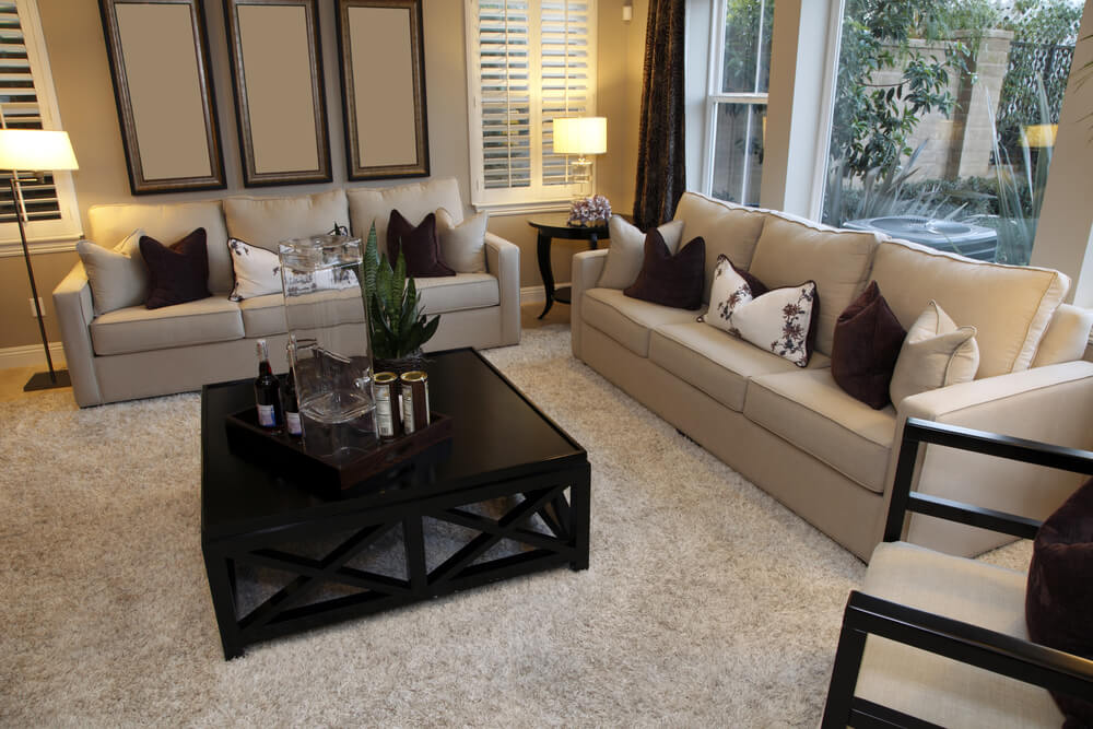Living room design with one dominant color being beige offset with a dark wood coffee table.