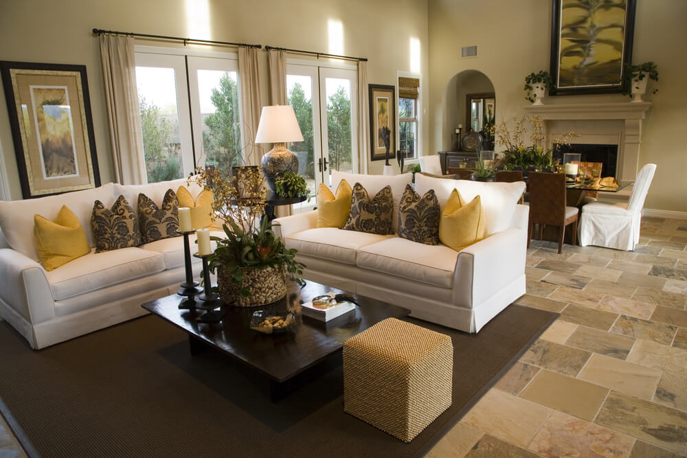 Large open concept home with dedicated living room comprised of two white sofas decorated with yellow and brown pillows.