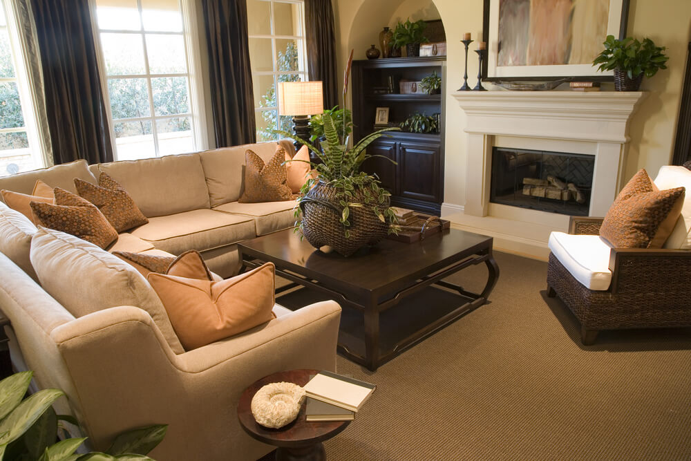Mediterranean inspired living room design with built-in shelving in arched recessions on both sides of the fireplace.