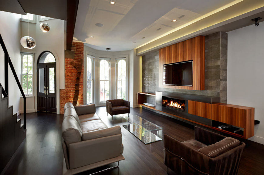Living room includes floor to ceiling front bay windows, near front door, with hidden lighting strip on side wall, recessed ceiling lights, and wall mounted fireplace.