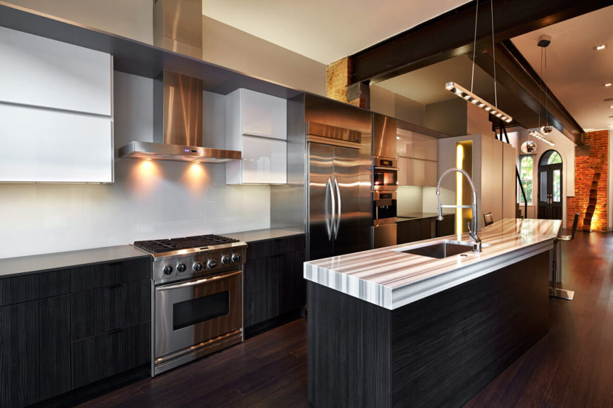 Kitchen features brushed metal appliances contrasting with alternately black and white cabinetry. Exposed metal I-beams are seen attached to small reveals of underlying brick work.