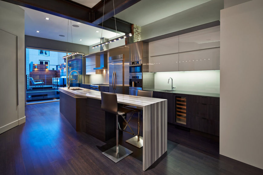 Here's a shot of the kitchen, showcasing the innovative layers of material and variety of textures across all surfaces. Angled island featuring bar style seating, built-in wine rack, minimalist cupboard doors, and drop ceiling all feature prominently. Rooftop deck is seen in background.