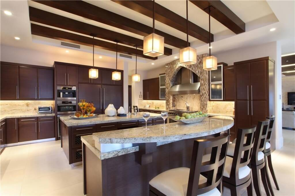 Dark brown wood provides excellent contrast in this expansive kitchen. Marble countertops lend elegance and atmosphere.