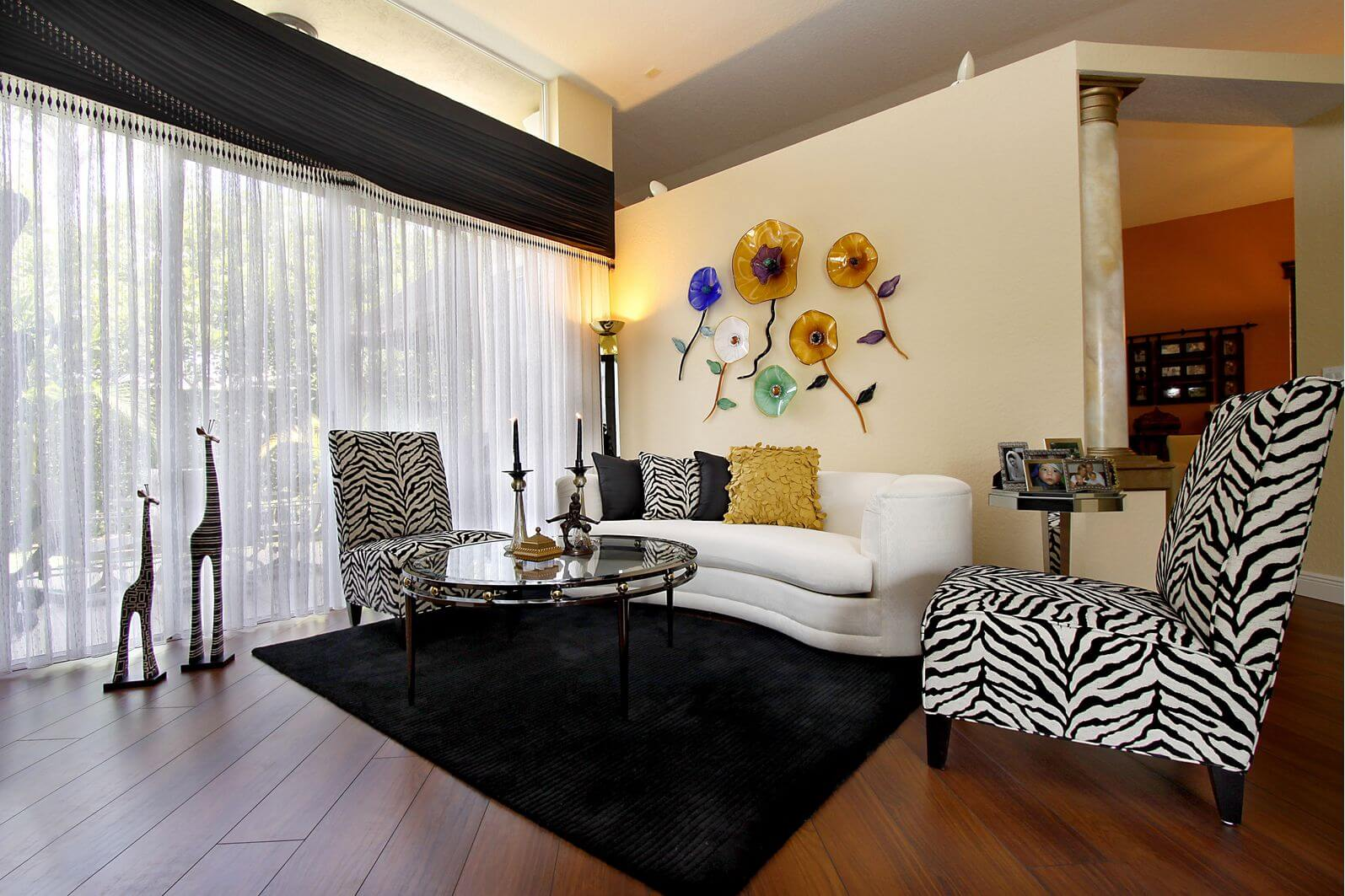Small living room with 2 zebra print armless chairs, one small white sofa, glass coffee table and black floor rug on wood flooring. This is a good example of zebra print furniture in a small living room design that looks good (i.e. not overdone).