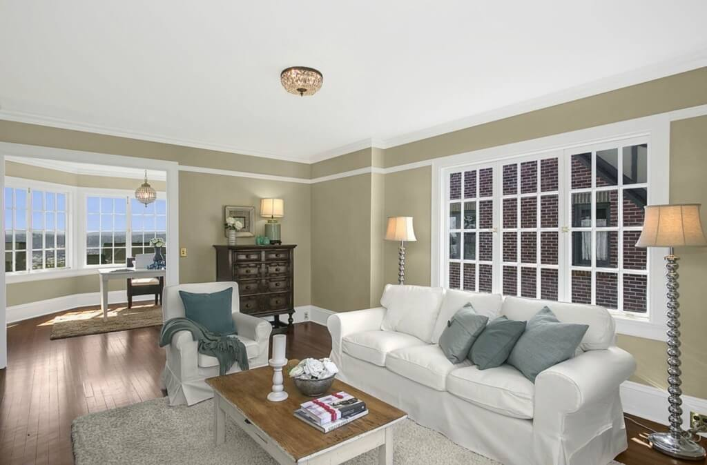 Family room extends from secondary office, featuring white sofa and matching rolled arm chair paired around natural wood topped coffee table. Expanse of windows behind sofa provide natural light, supplementing chromed flanking floor lamps.
