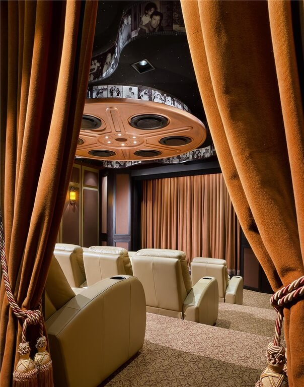 A private movie theater perfect for parties or household entertainment. The leather seats are a rich beige and the curtains are a bright orange that fits with the Moroccan accents the house favors.