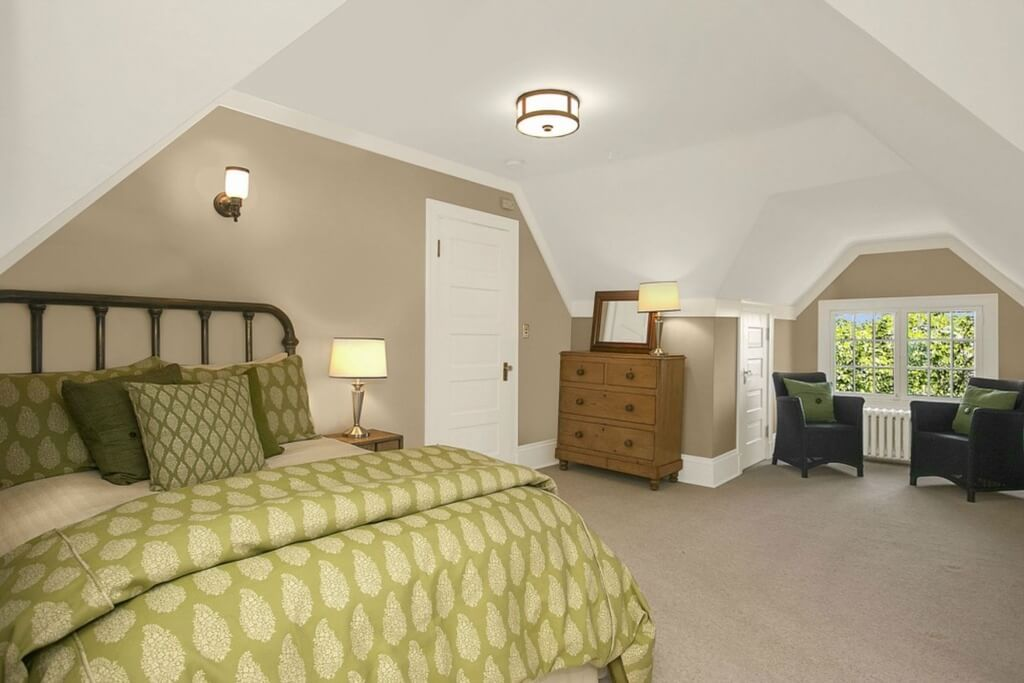 Upper floor bedroom features large green toned bed, natural wood dresser, and twin armchairs beneath low vaulted white ceiling.