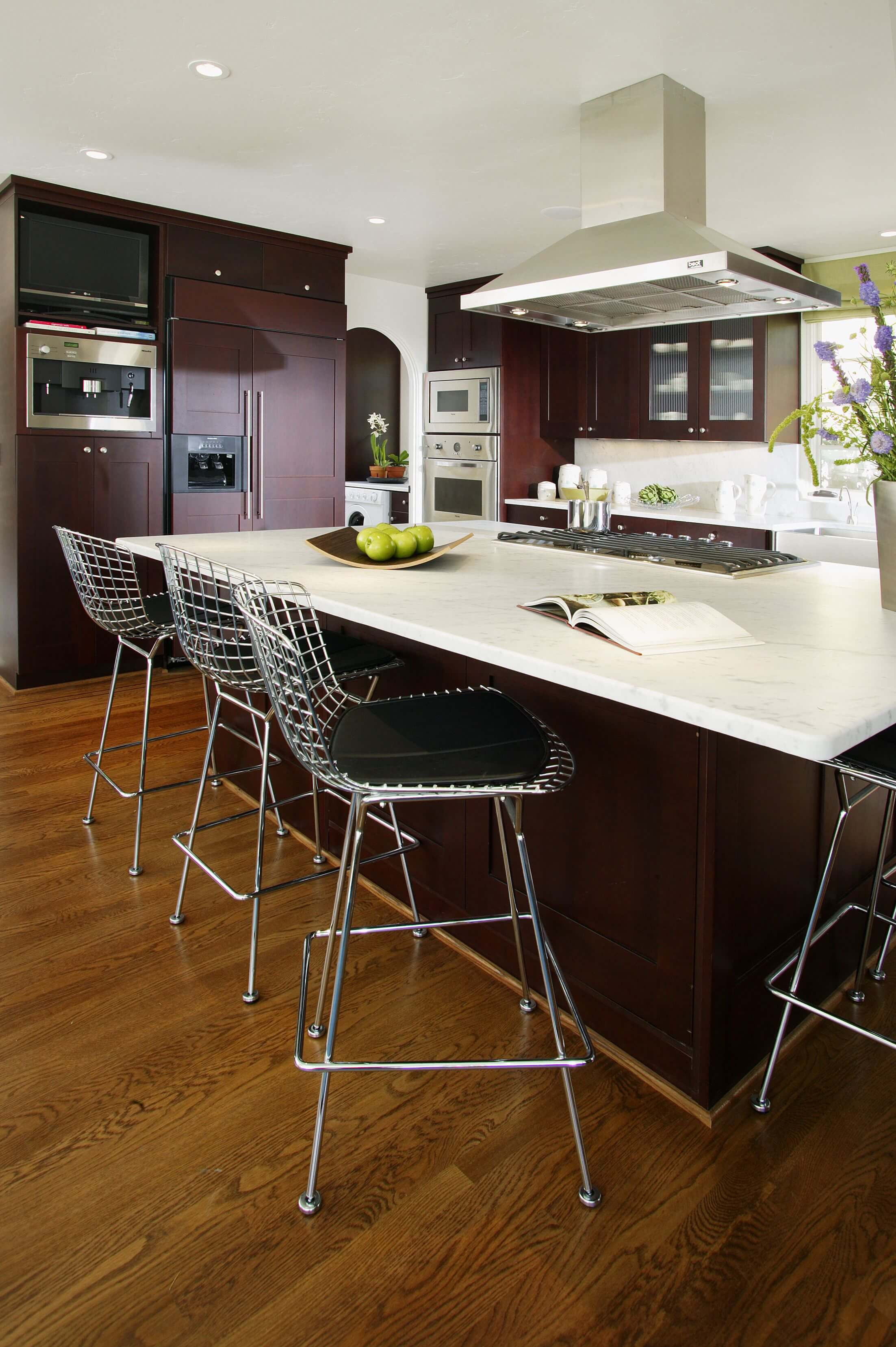 High contrast look in this kitchen, courtesy of dark stained cabinetry, white countertops, and bold, brushed aluminum appliances over natural hardwood floor.